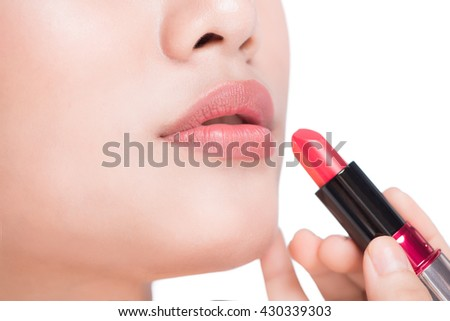 Asian young woman holding red lipstick. Close up portrait of attractive girl rouging her lips. Her mouth is gently open. Isolated on white background. - stock photo