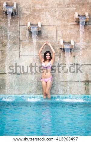 asian young woman in bikini enjoying the pool - stock photo