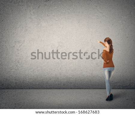 Asian young woman point somewhere on the wall, full length portrait. - stock photo