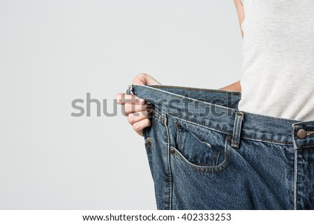 Asian young woman slim waist showing her old jean after successful diet weight loss slim waist concept - stock photo