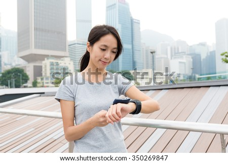 Asian Young Woman sync the data with her watch and mobile phone - stock photo