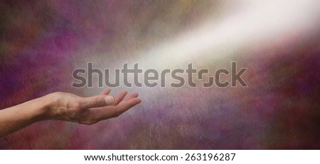 Ask Believe Receive - Female hand outstretched with a shaft of white light streaming across from the top right hand corner as if receiving energy on a wide dark colored rustic stone effect background  - stock photo