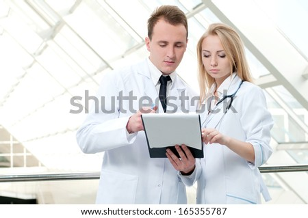 Asking for advise. Confident hospital colleagues writing in a notepad together - stock photo
