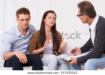 Asking for an expert advice. Frustrated young couple sitting on the couch while woman telling about their relationship problems to psychiatrist and gesturing - stock photo