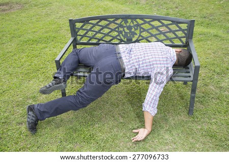 Asleep or drunk young man, outdoors on a park bench - stock photo