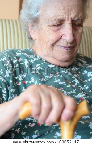 asleep senior woman holding wooden cane while she has a happy dream - stock photo