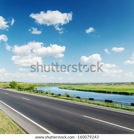 aspalt road near river under cloudy sky - stock photo