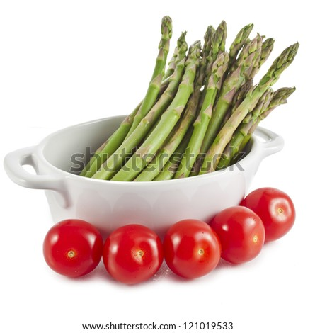 Asparagus and cherry tomatoes in pot  isolated on a white background - stock photo