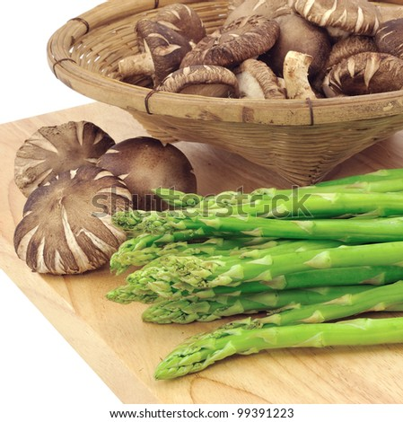 asparagus and mushrooms  on a cutting board - stock photo