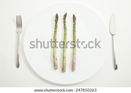 Asparagus in plate with fork and knife on white background - stock photo