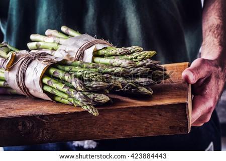 Asparagus. Raw asparagus. Fresh Asparagus.Green Asparagus. Tied asparagus in other positions. Farmer carries tied asparagus on a wooden board. - stock photo