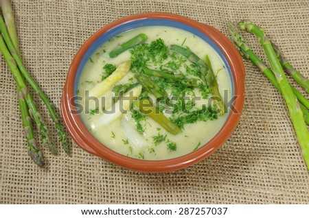 asparagus soup in plate on jute background - stock photo