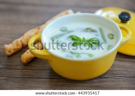 Asparagus soup with bread sticks on wooden table - stock photo
