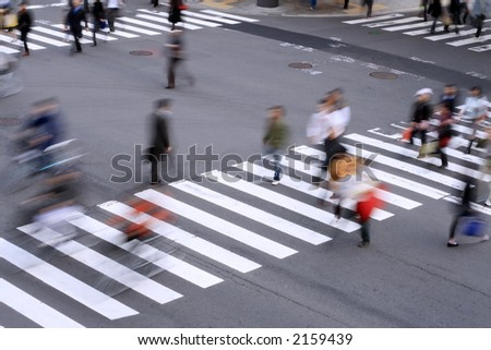 Aspect of a pedestrian cross with motion blurred aspect of the people. - stock photo