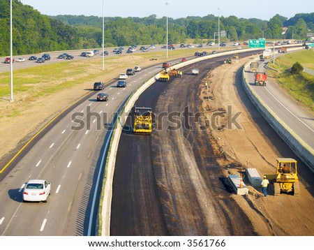 Asphalt being laid on freeway construction project - stock photo