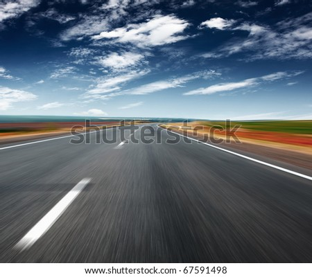 Asphalt blurred road and blue sky with clouds - stock photo