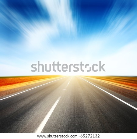 Asphalt blurry road and sky with blurry clouds - stock photo