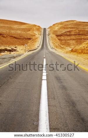Asphalt highway in stone desert in clear spring day - stock photo