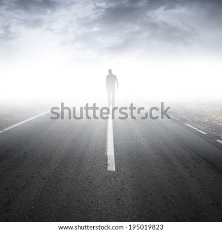 Asphalt highway perspective with walking man in the fog - stock photo