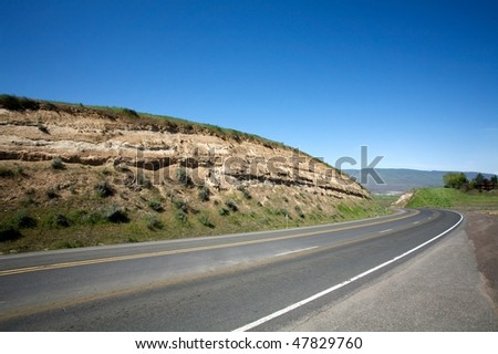 Asphalt highway winding on spring hills - stock photo