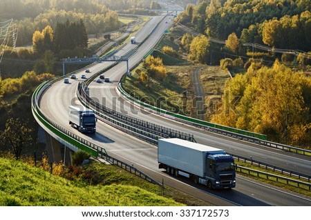 Asphalt highway with electronic toll gates in autumn woodland. Three trucks on the road. The bridge spanning the valley. View from above. Sunny day with bright fall colors. - stock photo