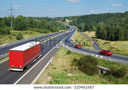 Asphalt highway with red truck and red passenger cars in wooded country. Slip road with traffic sign give way. Electronic toll gate in the distance. View from above. Sunny summer day with blue skies. - stock photo