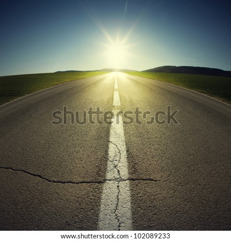 asphalt of country road in backlight - stock photo
