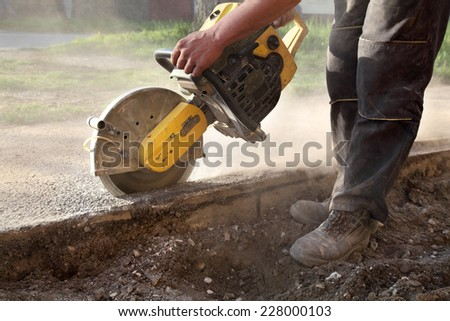 Asphalt or concrete cutting with saw blade at construction site - stock photo