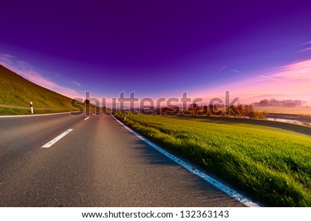 Asphalt Road along the Irrigation Canal and Dam in Switzerland, Sunrise - stock photo