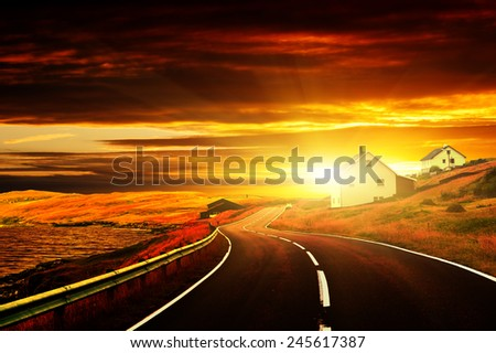 Asphalt road along the sea. Country houses. The Faroe Islands. Sunset. - stock photo