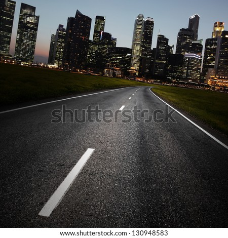 Asphalt road and a city with illuminated buildings on the horizon - stock photo