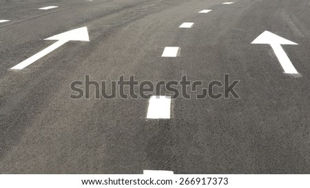 Asphalt road and arrow sign on surface road - stock photo