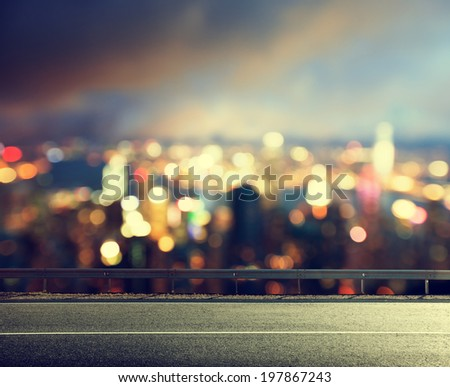 Asphalt road and blurred modern city - stock photo