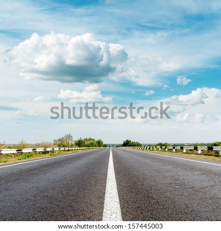 asphalt road and clouds over it - stock photo