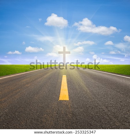 Asphalt road and crucifix with blue sky background. - stock photo