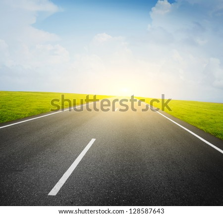 Asphalt road and green meadow and blue cloudy sky - stock photo
