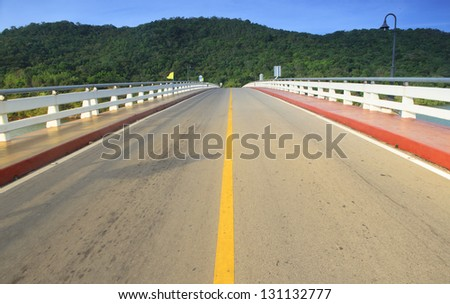 Asphalt road and mountain with blue sky - stock photo