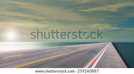 asphalt road and sea. - stock photo