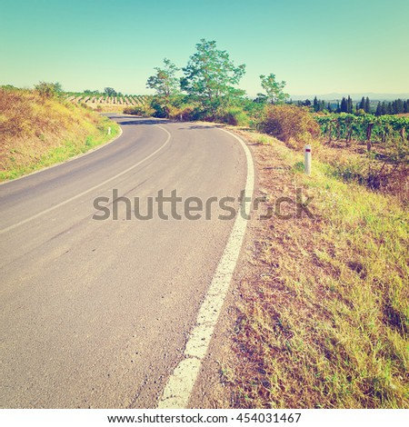 Asphalt Road between Autumn Vineyards in the Tuscany, Retro Effect - stock photo