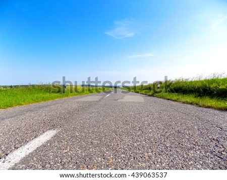 Asphalt road between fields during sunny day - stock photo