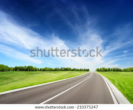 Asphalt road between grassy meadow with trees on horizon. Summer landscape with blue sky - stock photo