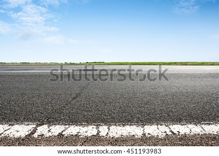 Asphalt road closeup with blue sky on horizon. Selective focus on foreground - stock photo