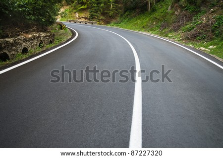 asphalt road curve with curve to the left - stock photo