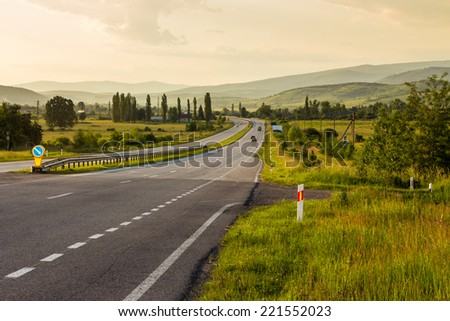 asphalt road going off into the distance on the left, passes through the green shaded forest and village in mountains - stock photo
