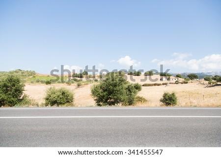 asphalt road in a desert scenery - stock photo
