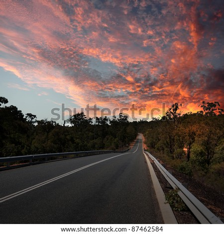 Asphalt road in countryside and cloudy sky - stock photo