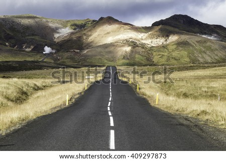 Asphalt road in Iceland leading into the mountains in the distance, - stock photo