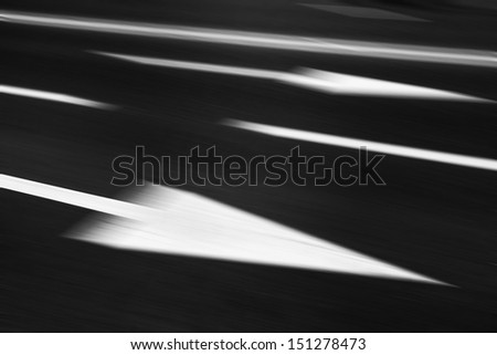 Asphalt road in motion blur with arrow. - stock photo