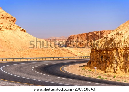Asphalt road in the desert of Israel on the way to Dead Sea - stock photo