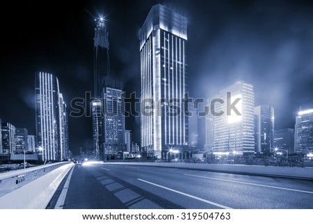 asphalt road near skyscrapers of a modern city at night - stock photo